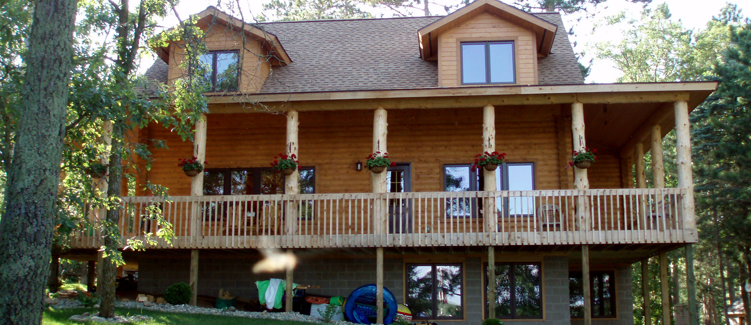 Exterior of a log home with a wrap around back porch